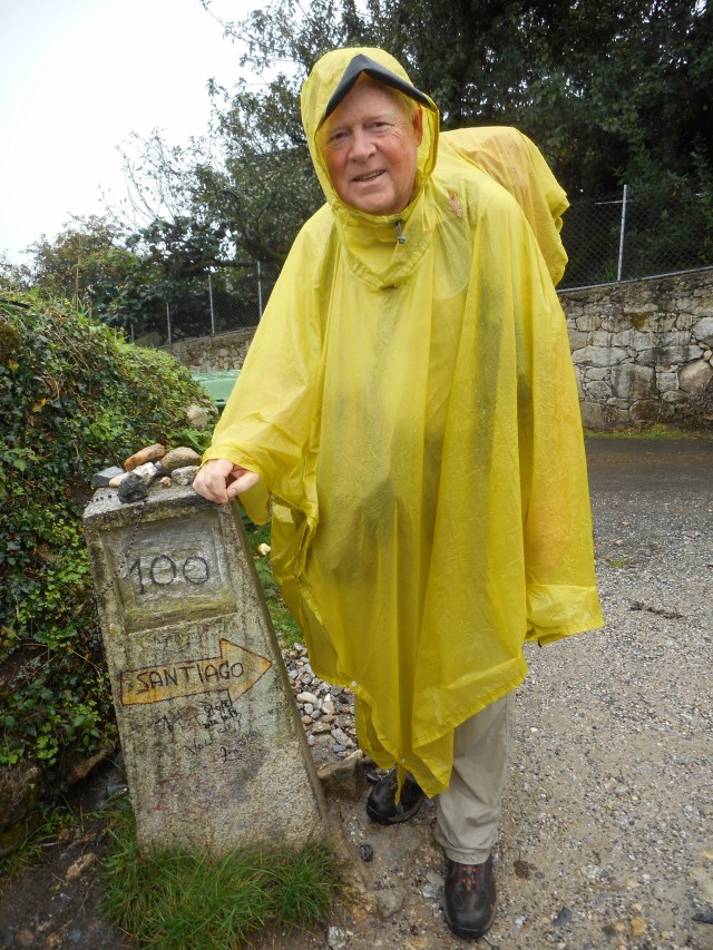 Standing by the magical 100 kilometer marker in the rain,